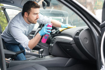 Man cleaning his car interiors