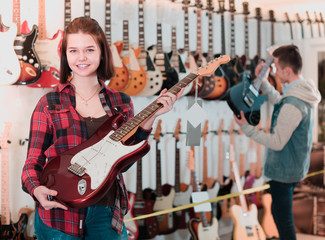 Attractive boy and girl teenagers examining electric guitars