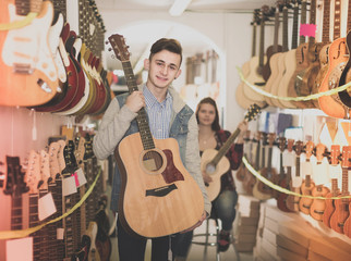 teenage customers deciding on suitable acoustic guitar in guitar shop