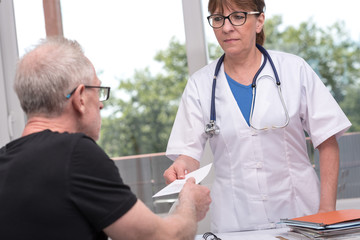 Female doctor giving prescription to her patient