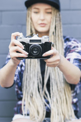 Young beautiful woman photographer is taking a photo. She has got long blond hair, full lips and green eyes
