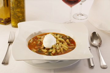 Runner bean soup arranged in a plate, Wineglass in background, Traditional dish in elegant setting, Selective focus with soft light