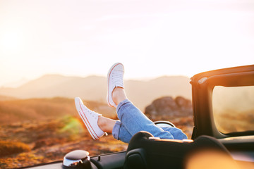 Happy woman rests and pushes her shoes out of the convertible to enjoy the view