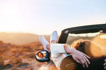 Young woman enjoying the sunset from a convertible