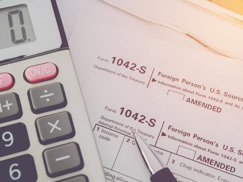 Top view calculator with pen on Tax Season: 1042 U.S. Individual Income Tax Return,