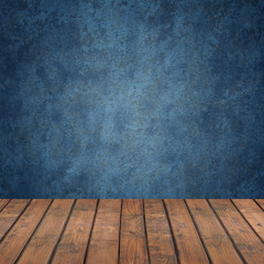 Empty wooden flooring against a blue wall