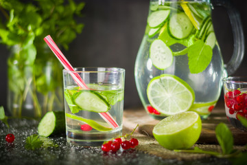 Water detox in a glass jar and a glass. Fresh green mint and berries. A refreshing and healthy drink.