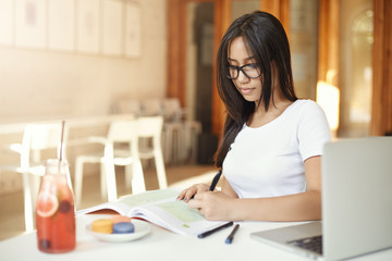 Asian female student doing homework at campus. Left-handed eastern girl working in a cafe, future lawyer or engineer.