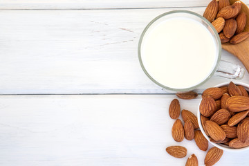 Close up top view of healthy the almond milk in drinking glass with seed in white cup and wooden spoon on white wooden table plate with copy space
