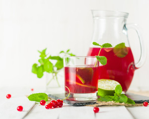 Compote in a glass jug and a glass. Berries and lime, red and green. Fresh mint leaves. Copy space.