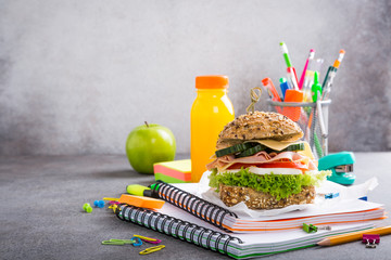 Healthy lunch for school with sandwich, fresh apple and orange juice. Assorted colorful school supplies. Copy space.