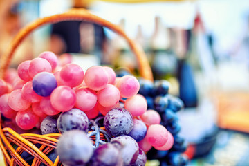 Grapes in a basket on the background of bottles of wine