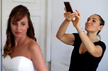 A woman takes pictures of a bride at the end of the make-up session before the wedding ceremony in Albissola