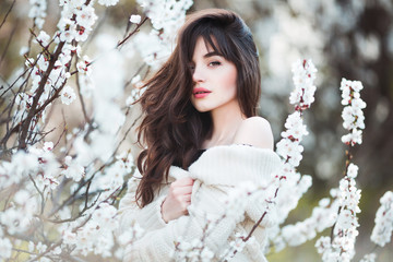 Happy beautiful young woman with long black healthy hair enjoy fresh flowers and sun light in blossom park.