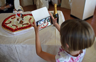 A child takes pictures of the wedding cake during a ceremony lunch in Savona