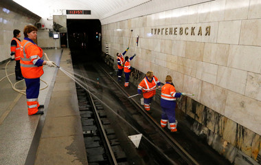 Employees wash the rail track and the walls at Turgenevskaya metro station in Moscow