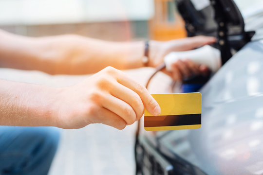 Male hand holding a credit card while charging an electric car