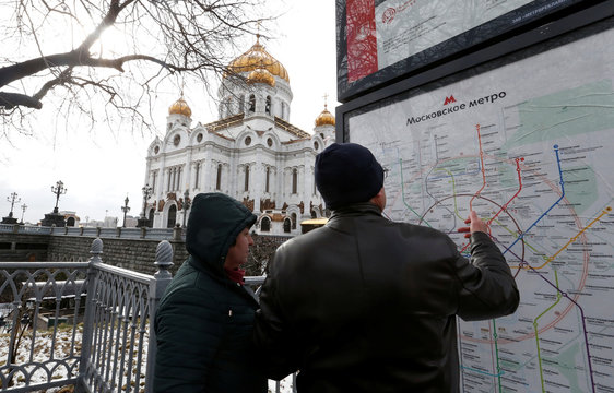 People examine a Moscow metro map in front of Christ the Savior cathedral in Moscow
