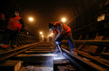 Employees repair the rail track in a tunnel at Sukharevskaya metro station in Moscow