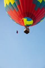 Bright balloon and basket in blue sky bottom view