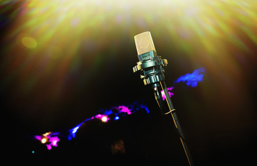 Microphone with golden rays of light. Retro microphone. A microphone on stage. A pub. Restaurant. Classic. Evening. Night show. European restaurant. European bar. American restaurant. American bar.