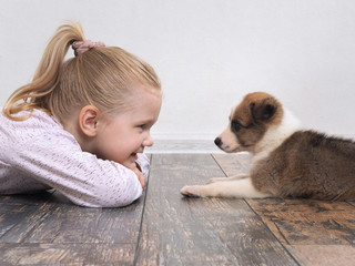 Lucky girl and little puppy in front of each other