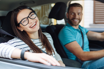 Happy woman sitting in the car next to her boyfriend Wall mural