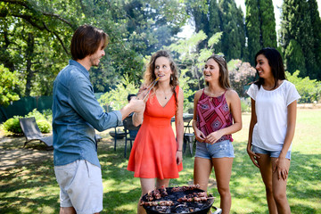 group of happy and cheerful young people having fun around barbecue grill during a summer holiday party outdoor in the garden