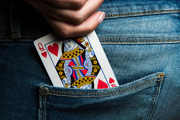 Queen of hearts card in woman jeans denim back trousers pocket