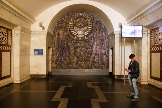 A man stands near an element of interior design with a sickle and a hammer at Paveletskaya metro station in Moscow