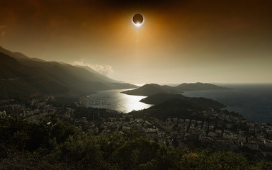Total solar eclipse in dark red glowing sky above seaside city