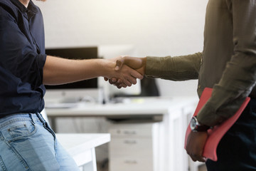 Close up of two young colleagues shaking hands