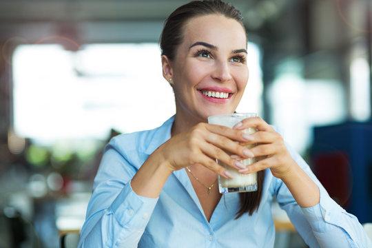 Woman drinking latte macchiato at cafe