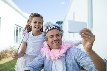 Father and daughter taking selfie on mobile phone