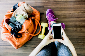 Woman holding smartphone with fitness equipment