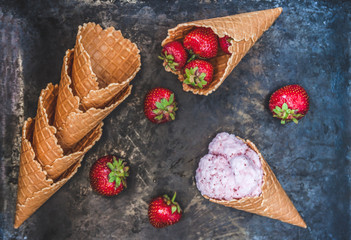 Waffle cone with strawberry ice cream, spoon for ice cream and fresh berries on a dark background, toning in retro style