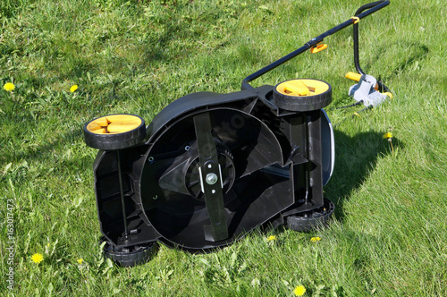 A cheap plastic electric lawn mower lies on its side on a spring lawn.