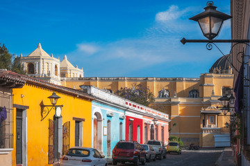 Sunny afternoon on the main street in Antigua Guatemala with colorful heritage houses.