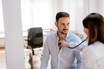 Doctor examining male patient in hospital with sthetoscope