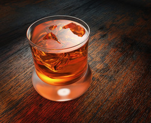 Glass with whisky on a wooden background