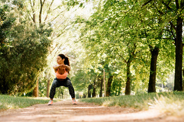 Beautiful woman working out in summer park