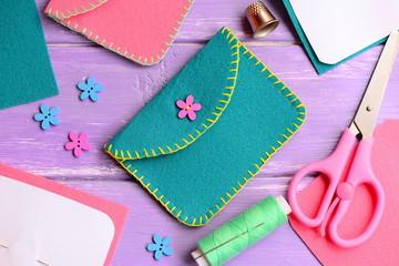 Nice felt purse with flower wooden button. Scissors, thread, needle, thimble, paper templates, flower wooden buttons on a wooden table. Kids hand sewing workshop concept