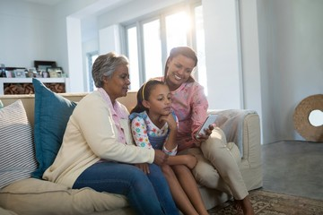 Happy family using mobile phone in living room