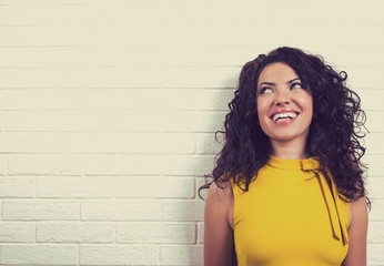 Laughing happy woman, isolated on brick wall background