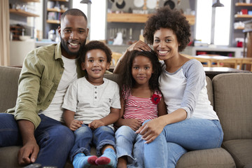 Portrait Of Happy Family Sitting On Sofa In Open Plan Lounge