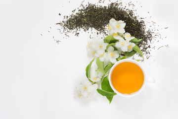 Jasmine dry green tea leaves with fresh jasmine flowers and cup of tea on white background.