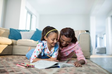 Mother assisting her daughter with drawing in living room