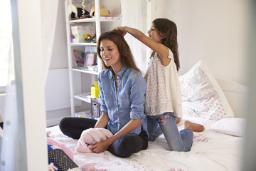 Daughter Brushes Mother's Hair As They Sit In Girl's Bedroom