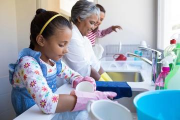 Family washing utensils in kitchen sink