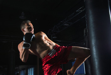 Deurstickers Vechtsport The fighter of mixed martial arts with a shout is hitting the bag